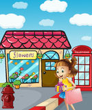 A girl near the flowershop holding a bag and a gift Royalty Free Stock Photography