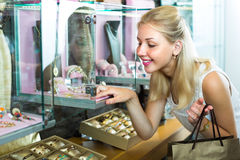 Girl near glass showcase in bijouterie store Stock Photography