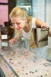 Girl near glass showcase in bijouterie store Stock Images