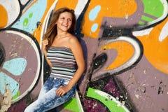 Girl near graffiti wall background. Royalty Free Stock Photography