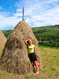 Girl near the haystack. Haystack and girl on the background of the countryside stock photography