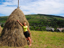 Girl near the haystack. Haystack and girl on the background of the countryside royalty free stock photos