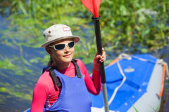 Girl near a kayak on the river Royalty Free Stock Photo