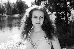 Girl near the lake. Black-and-white portrait of the beautiful girl posing near the lake royalty free stock photography