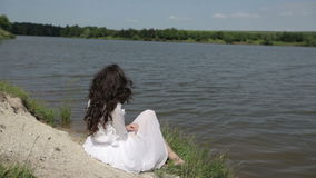 Girl near the lake. Girl with luxurious black hair sitting on the river bank stock footage