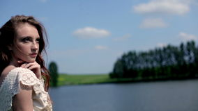 Girl near the lake. Red-haired girl posing for a photographer near a lake stock footage