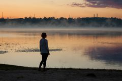 A girl near the lake in the summer morning. A girl stand near the lake. Sunrise and lake on the background stock images