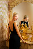 Girl near luxury mirror. Beautiful blond girl near luxury the mirror Stock Image