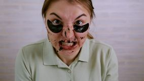 The girl near the mirror carries out cosmetic procedures on her face. The girl puts Korean makeup on the area under her