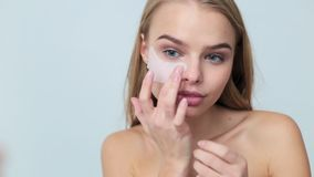 The girl near the mirror conducts beauty treatments on the face . The girl puts patches on the area under the eyes stock video footage