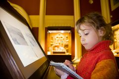 Girl near monitor writes at excursion in museum. Little girl standing near monitor writes to writing-books at excursion in historical museum against exhibits of Royalty Free Stock Images