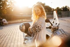 Girl near the moped at sunset royalty free stock photo