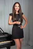 Girl near the piano with a glass of wine Stock Photography