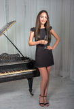 Girl near the piano with a glass of wine Royalty Free Stock Photo