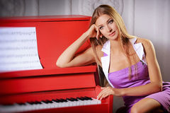 Girl near the piano Royalty Free Stock Photos