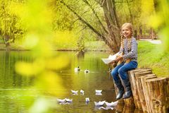Girl near pond playing with paper boats in forest Royalty Free Stock Image