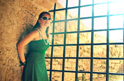 Girl near prison bars. Girl in green standing against a wall next to prison bars. Flare effect and dramatic lighting stock photography