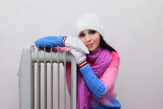 Girl  near a radiator heated Royalty Free Stock Photography