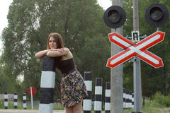 Girl near railroad's traffic sign Royalty Free Stock Photography