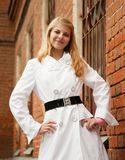 Girl  near red brick house. Pretty girl in white cloak near red brick house Royalty Free Stock Photography