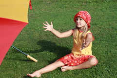 Girl near by the red and yellow umbrella. Barefoot little girl in red and yellow dress sitting near by a red and yellow umbrella and catching something stock photo