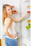 Girl near the refrigerator Royalty Free Stock Image