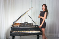 Girl near the retro piano with a glass of wine. Girl in a cocktail dress near the retro piano with a glass of wine Stock Image