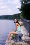 The girl near the river. Girl is sitting on the quay by the river Stock Photos