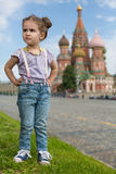 Girl near the Saint Basils Cathedral. Little girl in jeans with suspenders near the Saint Basils Cathedral with hands on hips royalty free stock photography
