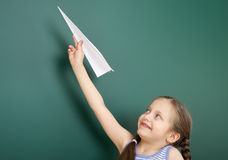 Girl near school board with paper airplane Royalty Free Stock Photography