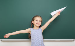 Girl near school board with paper airplane Royalty Free Stock Photos