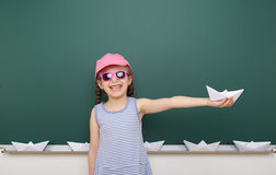 Girl near school board with paper plane and boat Stock Images