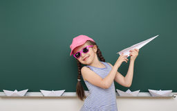 Girl near school board with paper plane and boat Royalty Free Stock Photography