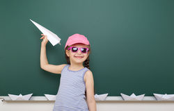 Girl near school board with paper plane and boat Stock Photos