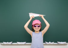Girl near school board with paper plane and boat Stock Photography