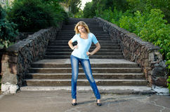 Girl near the stairs. Beautiful blondie girl standing near the stairs in the park Stock Photo
