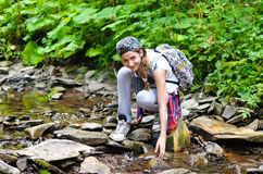 Girl near stream water in mountain. Stock Photography