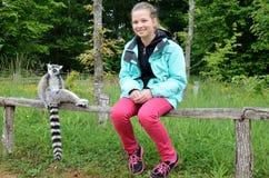 A girl near the tame lemur Stock Photos
