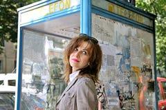 Girl near a telephone cabin Stock Photography