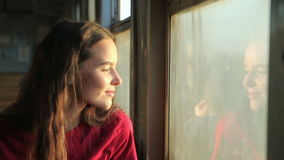 The girl near the train car window. A young, beautiful girl is traveling by train sitting near a window. The morning sun illuminates her face. The joy of stock footage