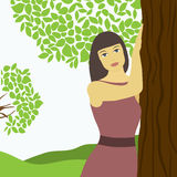 Girl near the tree. Girl near a tree on the background of the summer landscape Royalty Free Stock Image