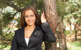 Girl near a tree. Young girl in a black jacket near the tree Royalty Free Stock Photo