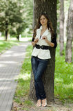 The girl near a tree in park. The harmonous nice girl with long hair costs  near a tree in park Royalty Free Stock Photo