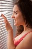 Girl near venetian blinds in the morning Stock Images