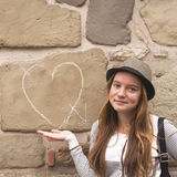 Girl near a wall painted chalk heart and arrow. Royalty Free Stock Photography