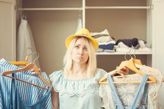 Girl near a wardrobe with clothes can not choose what to wear. Heavy Choice Concept has nothing to wear.  stock images