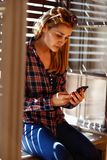 Girl near window looking in cell phone Royalty Free Stock Photos
