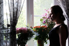 The girl near the window. The girl thought for a moment, standing near the window with flowers Stock Photo