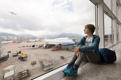 Girl near the window waiting her flight in the airport Royalty Free Stock Images