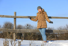 Girl near wooden fence in winter royalty free stock photography